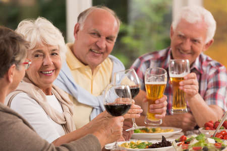 Photo for Happy elderly friends drinking beer and wine during dinner - Royalty Free Image