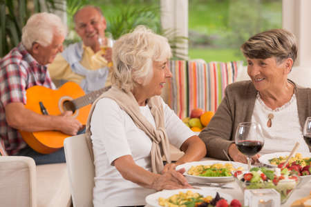 Photo for Two senior women talking and drinking wine, in the background elderly man playing a guitar - Royalty Free Image