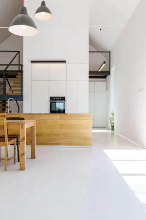 Photo pour Modern minimalist kitchen with wooden furnitures, white walls and high ceiling - image libre de droit
