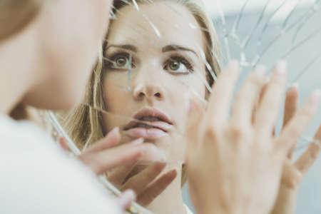 Photo pour Face of schizophrenic woman reflected in broken mirror - image libre de droit