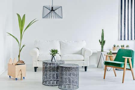 Foto de Living room with green armchair, openwork table and sofa - Imagen libre de derechos