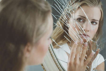 Foto de Beautiful woman with mental disorder touching broken mirror - Imagen libre de derechos