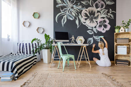 Photo pour Woman drawing flowers on chalkboard wall in multifunctional home interior - image libre de droit