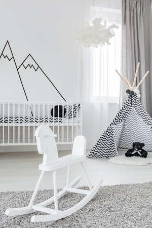 Foto de Baby girl room with white rocking horse and play tent - Imagen libre de derechos