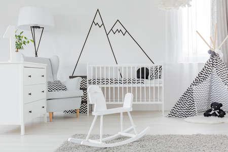 Foto de Child bedroom with decorative wall decal, dresser and cot - Imagen libre de derechos