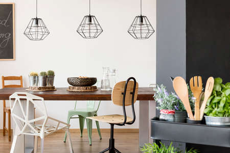 Photo pour Room with communal table, chairs, pendant lamps, kitchen cart - image libre de droit