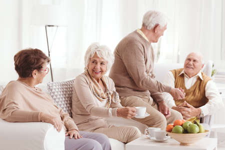 Photo pour Group of seniors talking and drinking coffee - image libre de droit