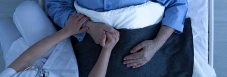 Photo pour Photo from the top of nurse holding older sick man's hand who lies in hospital bed - image libre de droit