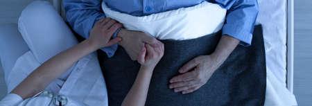 Foto de Photo from the top of nurse holding older sick man's hand who lies in hospital bed - Imagen libre de derechos