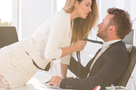 Photo pour Shot of a beautiful woman sitting on a desk in an office and holding elegant man's tie - image libre de droit