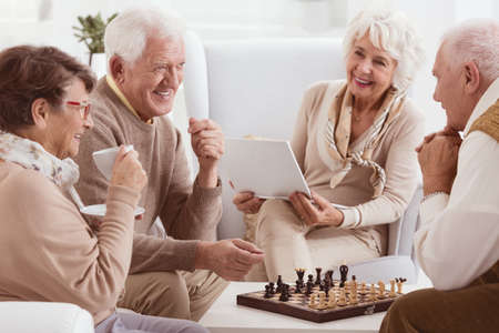 Photo pour Happy pensioners of rest home playing chess - image libre de droit
