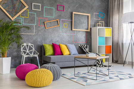 Photo pour Spacious modern lounge with grey sofa and colorful pillows and poufs - image libre de droit