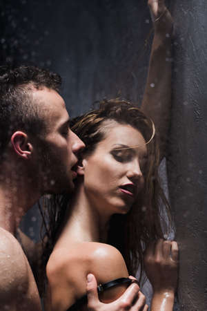 Photo pour Naked man passionately kissing a woman in her ear while showering - image libre de droit