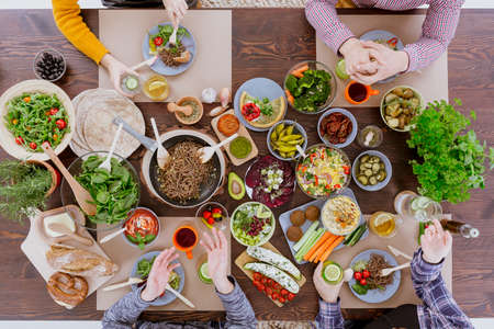Foto de Various vegan and vegetarian food lying on rustic table - Imagen libre de derechos