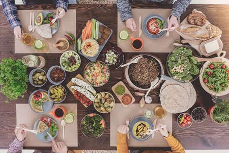 Photo pour People eating healthy lunch, sitting beside rustic table - image libre de droit