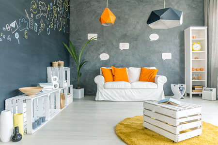 Photo for Room with chalkboard wall, sofa and white crate furniture - Royalty Free Image