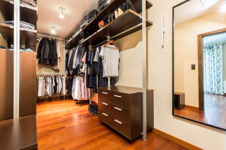 Photo pour Private spacious walk-in closet full of clothes and shoes with wooden wardrobes - image libre de droit