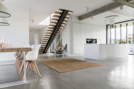 Photo pour Open floor apartment with staircase, dining table and kitchen - image libre de droit