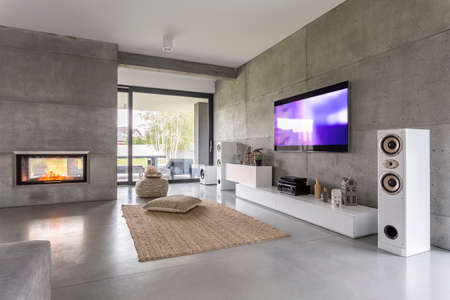 Photo for Tv living room with window, fireplace and concrete wall effect - Royalty Free Image