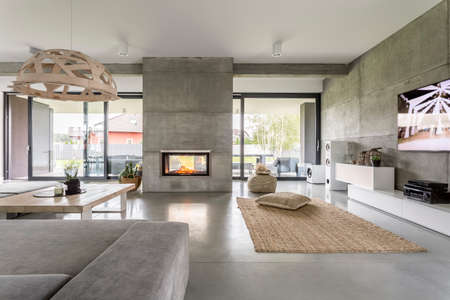 Photo pour Spacious villa interior with cement wall effect, fireplace and tv - image libre de droit