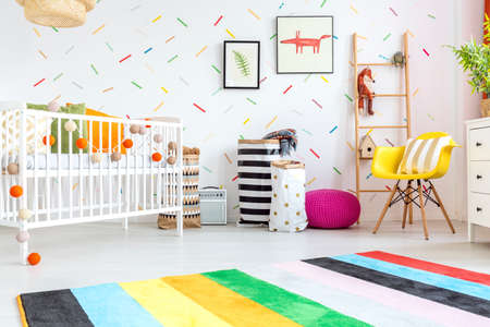 Photo pour Baby room with yellow chair and white cot - image libre de droit