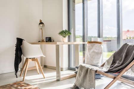 Foto de White room with deckchair, wooden desk, chair and window wall - Imagen libre de derechos