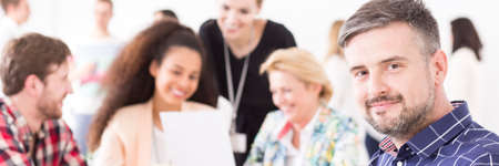 Confident smiling man participating in a company meeting, with other members in the blurry background