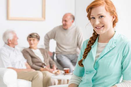 Foto de Smiled nurse at retirement home with seniors - Imagen libre de derechos