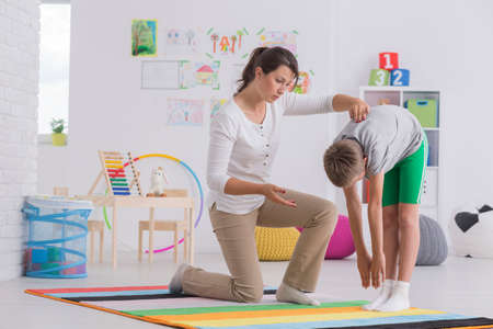 Photo for Child standing forward bend while exercising with physiotherapist - Royalty Free Image