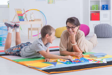 Foto de Tutor and child lying on the floor, learning together - Imagen libre de derechos