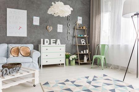 Foto de Modern studio apartment with pastel furniture and big window - Imagen libre de derechos