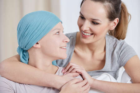Photo pour Hopeful cancer woman wearing headscarf, talking with friend - image libre de droit