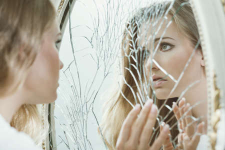 Photo pour Young pretty girl with teenage problems looking in the broken mirror - image libre de droit