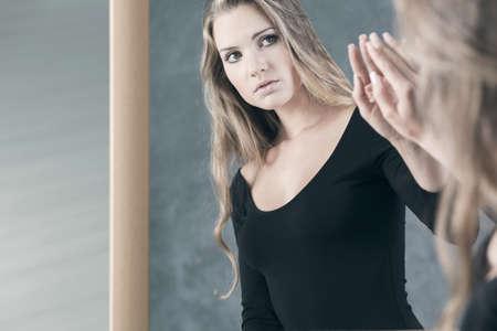 Photo pour Teenage girl with schizophrenia afraid of her mirror reflection - image libre de droit