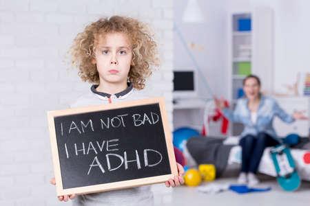 Foto de Sad ADHD boy holding small board, shouting mother in background - Imagen libre de derechos