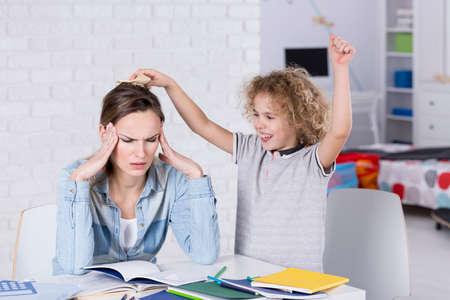 Foto de Child annoying his tired mother with headache - Imagen libre de derechos
