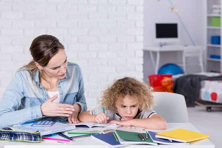 Foto de Mother and child having problem with concentration while doing homework - Imagen libre de derechos