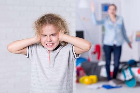 Foto de Misbehaving child covering his ears, mother shouting in background - Imagen libre de derechos