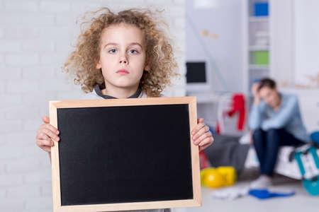 Foto de Sad child boy with curly hair holding small blackboard - Imagen libre de derechos