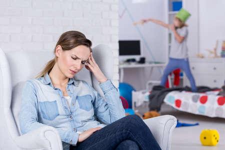 Foto de Tired mother of hyperactive child having headache - Imagen libre de derechos