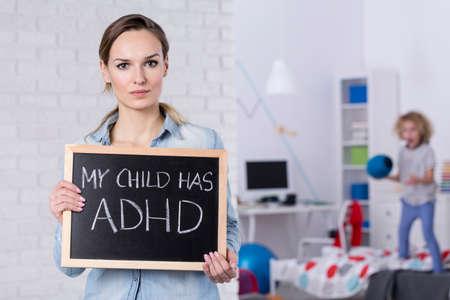 Foto de Mother of child with ADHD holding small blackboard with text - Imagen libre de derechos
