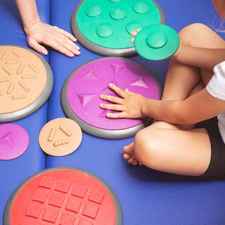 Foto de Child with occupational therapist touching sensory integration equipment - Imagen libre de derechos