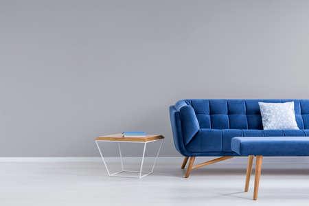 Foto de Grey room with blue couch, bench and side table - Imagen libre de derechos