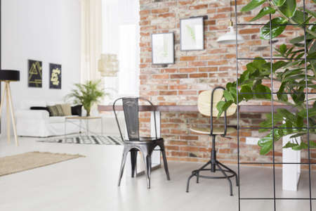 Photo pour Loft interior with dining table, brick wall and green plant - image libre de droit