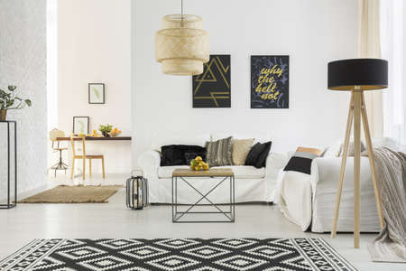 Foto de Bright room with white sofa, table, pattern carpet and lamp - Imagen libre de derechos