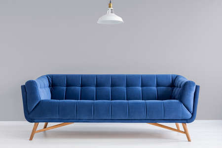 Photo for Grey interior with stylish upholstered blue sofa and lamp - Royalty Free Image