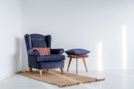 Foto de White interior with navy blue armchair, rug and side table - Imagen libre de derechos