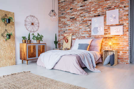 Photo for Bright bedroom with double bed, brick wall and rug - Royalty Free Image