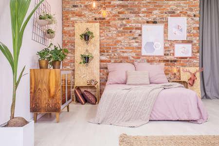 Foto de Bedroom with double bed, brick wall and green decorative plants - Imagen libre de derechos