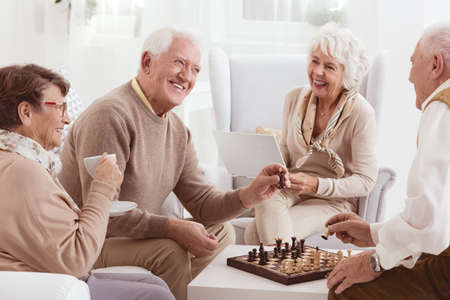 Photo pour Aged people playing chess together in day-care center - image libre de droit